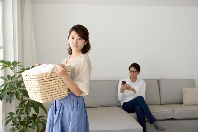 洗濯物をする女性とスマホ男性